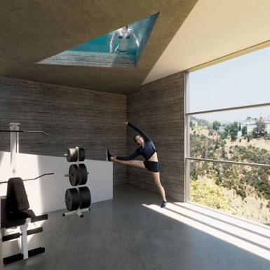 Interior view of modern, light-filled board-formed concrete gym. Vertical sliding windows open for a view of the surrounding landscape and skyline, with a ceiling window revealing the pool above.