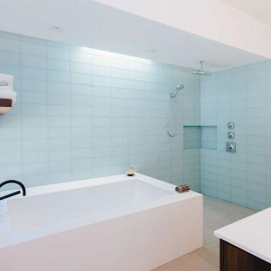 Ranch Redux - Interior view of the modern, light-filled master bathroom. A narrow skylight illuminates the light blue glass tile along the shower and soaking tub. Photograph by Tomoko Matsubayashi.
