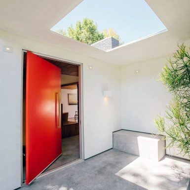 Ranch Redux - Exterior view of the front porch and red door. A large skylight and built-in bench complement the space. Photograph by Tomoko Matsubayashi.