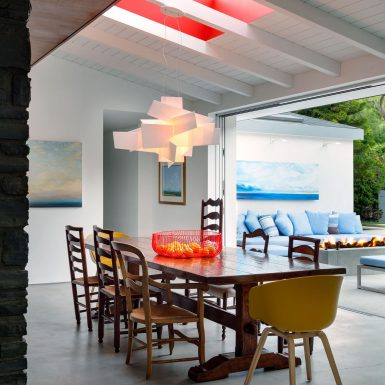 Ranch Redux - Bright natural light in modern dining room with skylight, & view of outdoor firepit through sliding door. Photograph by Trevor Tondro.