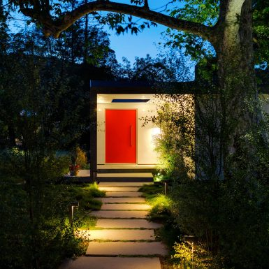 Ranch Redux - Exterior view of red front door at dusk, with landscape and modern paver walkway lit with warm pathway lighting in the foreground. Photograph by Trevor Tondro.