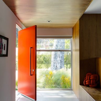 Ranch Redux - Interior view of entry and red front door, with wood ceiling and bench. Photograph by Trevor Tondro.