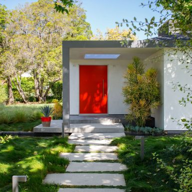 Ranch Redux - Exterior view of red front door and skylight. Modern concrete paver pathway and grassy landscape in the foreground. Photograph by Trevor Tondro.
