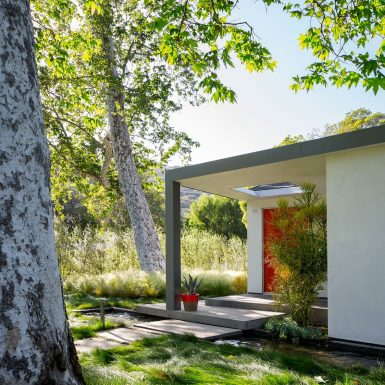 Ranch Redux - Exterior view of front porch with red front door and grassy landscape, with water feature below and sycamore trees overhead. Photograph by Trevor Tondro.