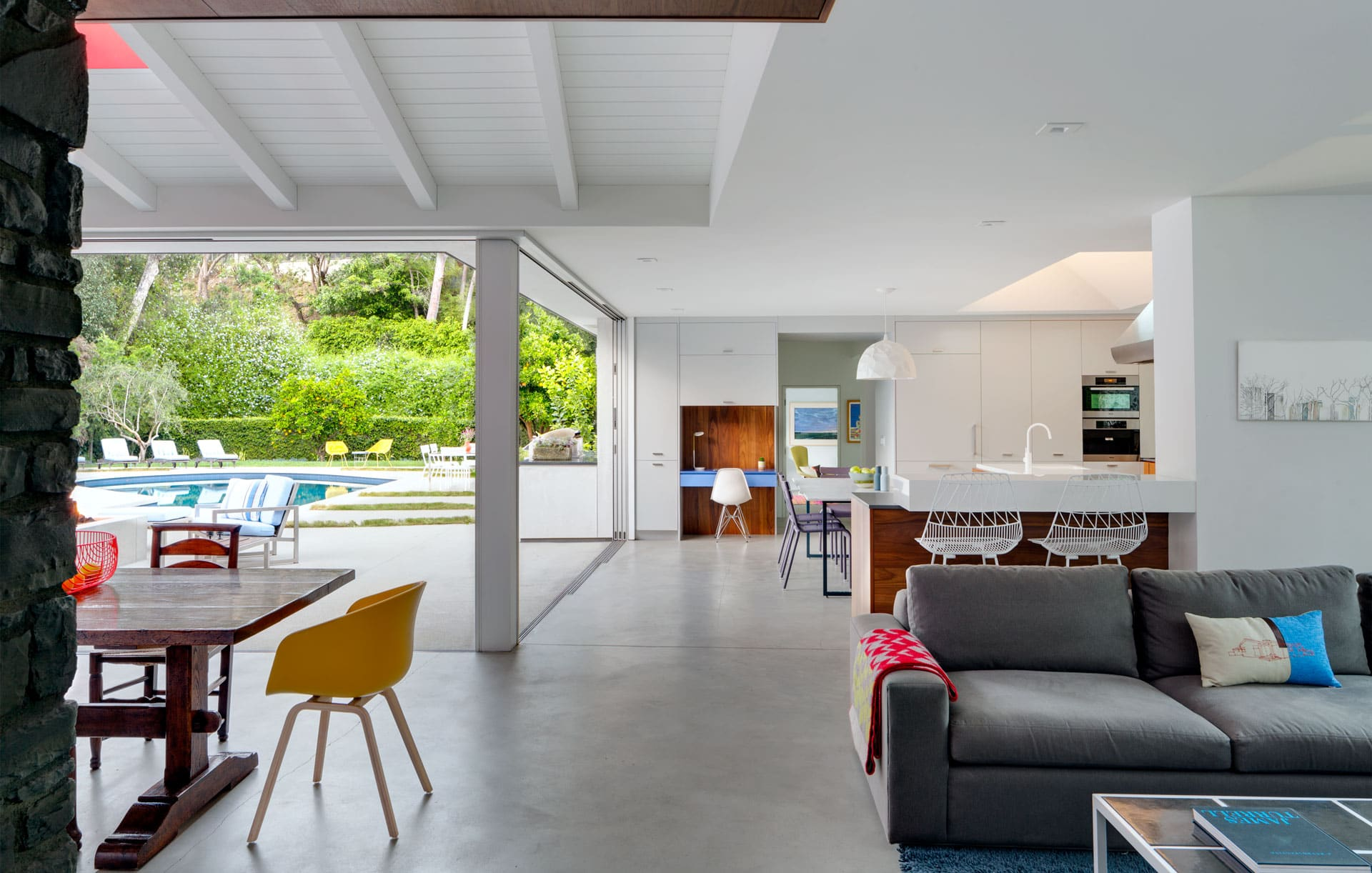 Ranch Redux - Interior view of light-filled modern den and kitchen, with pool visible through sliding doors. Photograph by Trevor Tondro.