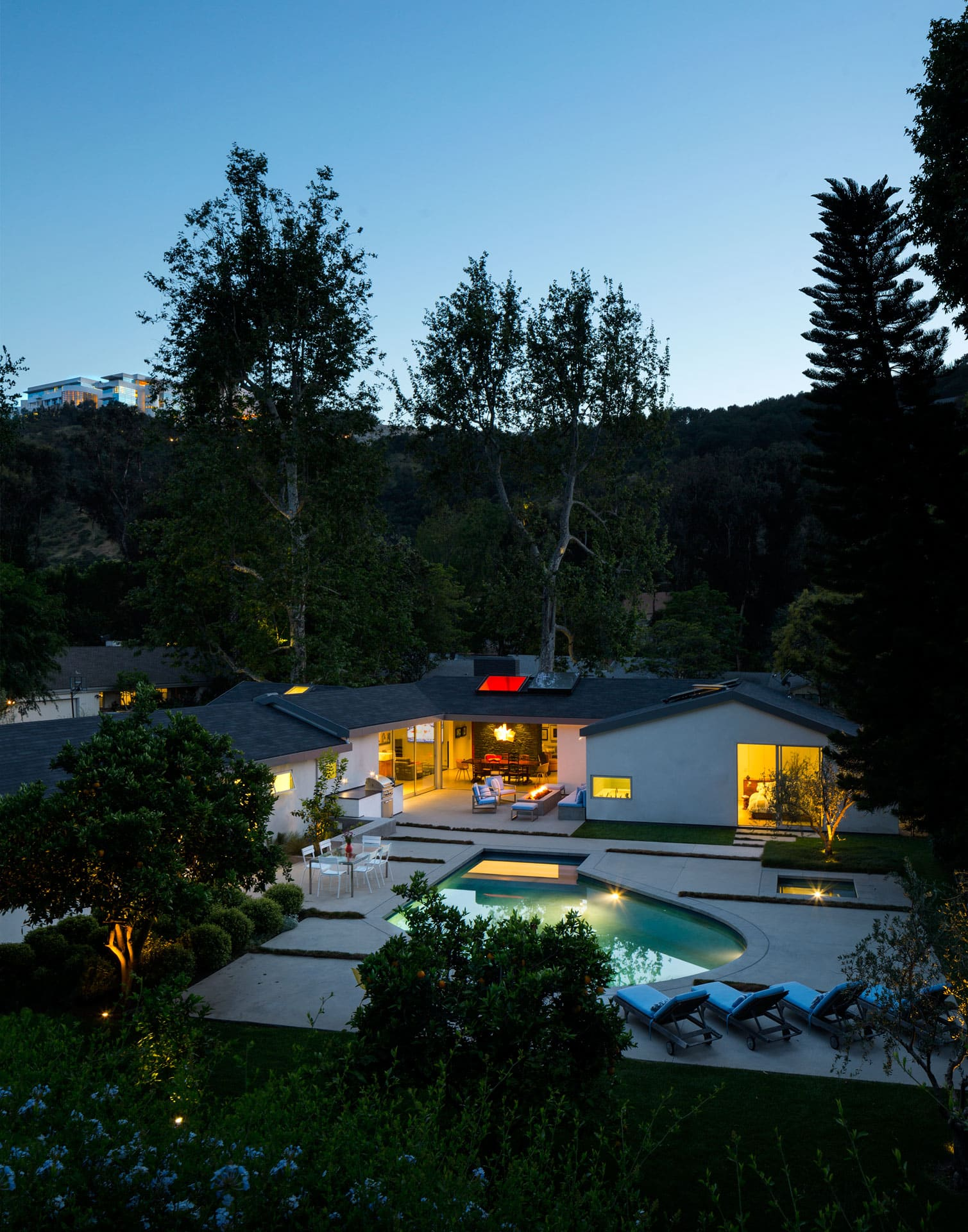 Ranch Redux - Exterior view from above at dusk, with warmly-lit pool and patio. Sycamore trees and the nearby Getty rise up in distance. Photograph by Trevor Tondro.